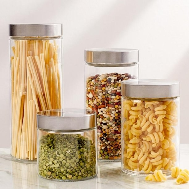 Product photo showing Estilo glass canisters of various sizes filled with pasta, beans, and lentils