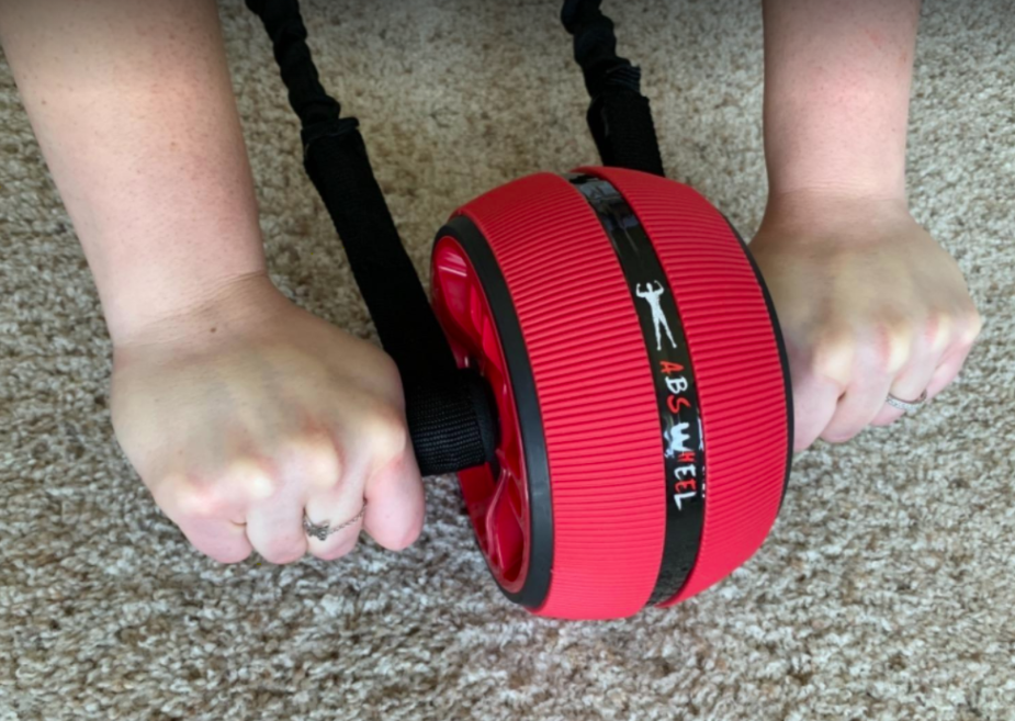 Reviewer uses red ab roller wheel to work their core on their carpeted floor