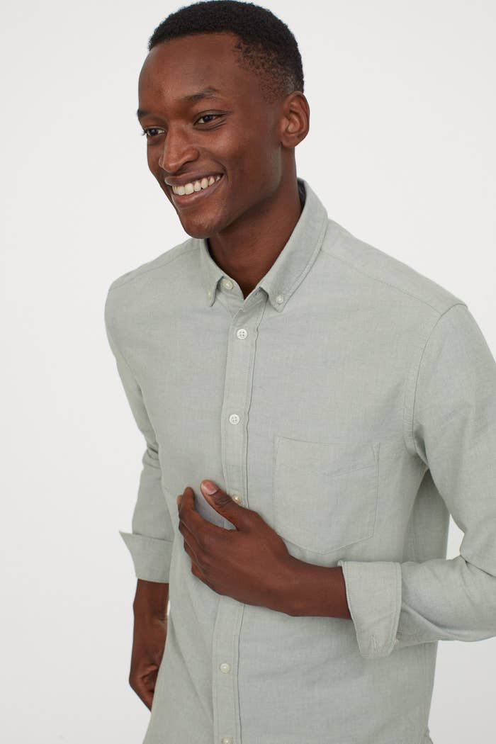 Model wearing a pale khaki green oxford shirt with sleeves rolled up