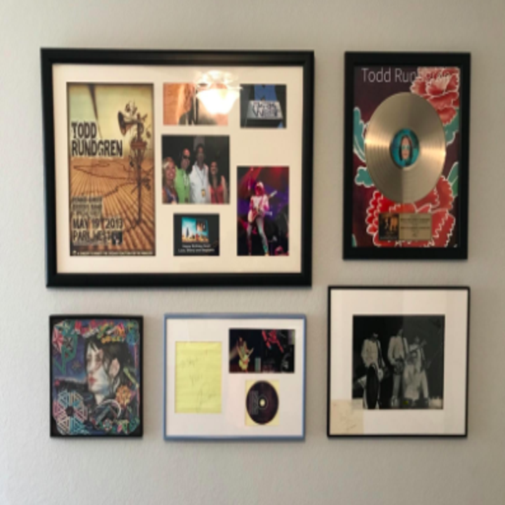 reviewer's pic of gallery wall of various sized framed items using the hanger