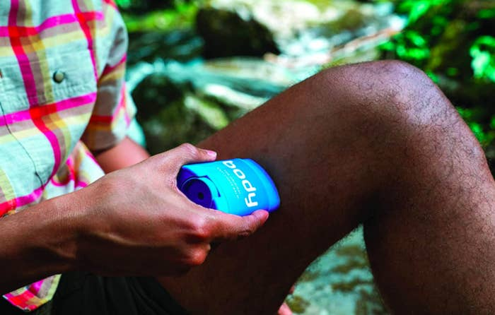 Model applies blue container of Body Glide Original Anti-Chafe Balm to their thigh outside