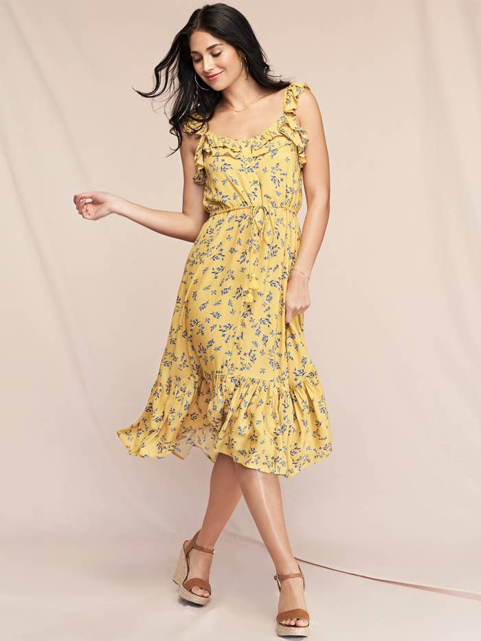 Model in a yellow floral flutter dress