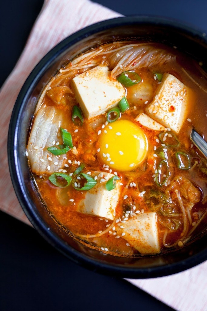A black bowl full of rich, spicy looking broth dotted with kimchi, soft tofu, sliced green onion, and a runny egg yolk in the middle