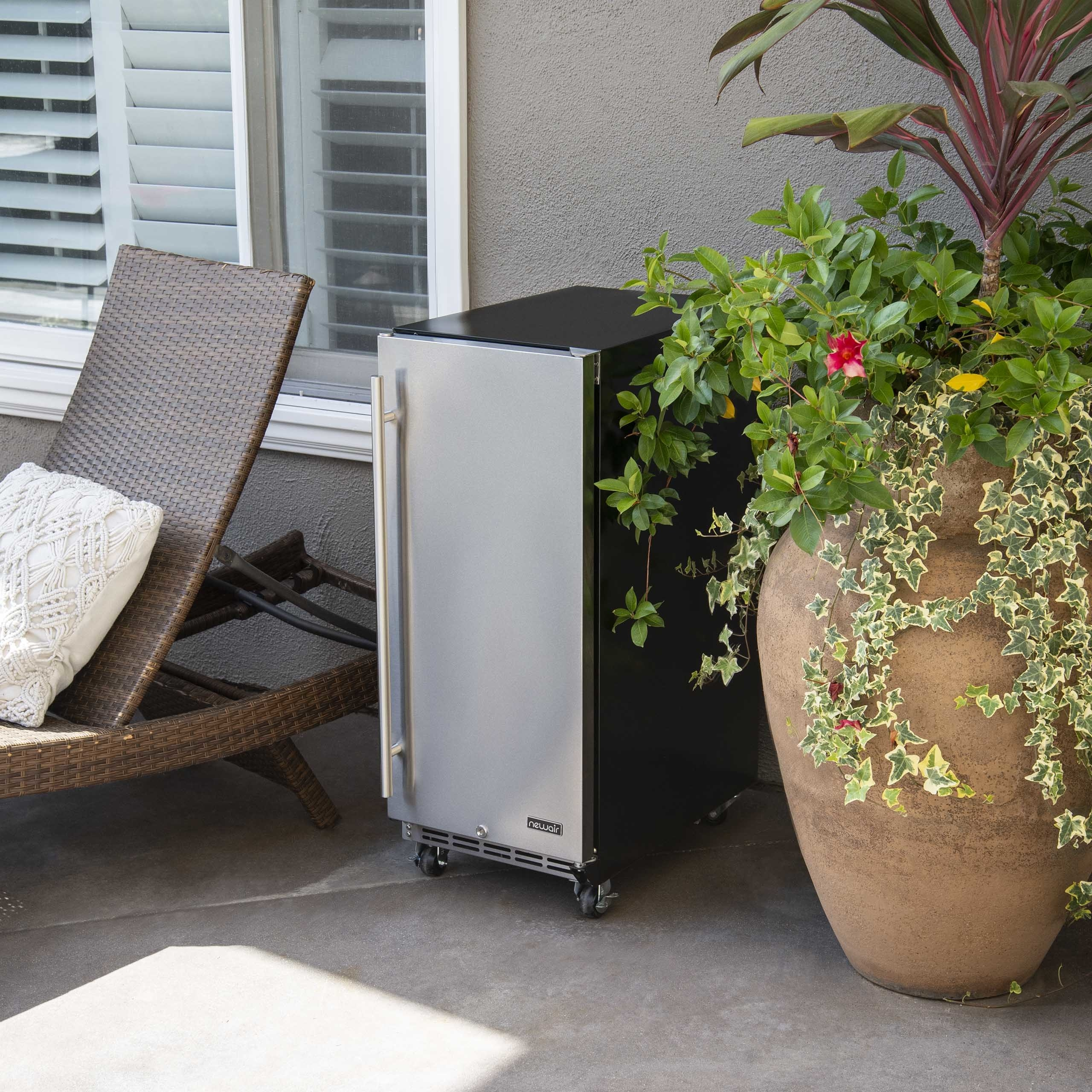 """The stainless steel NewAir 15"""" Built-in 90 Can Outdoor Rated Beverage Fridge with Auto-Closing Door and Easy Glide Casters on a back patio"""