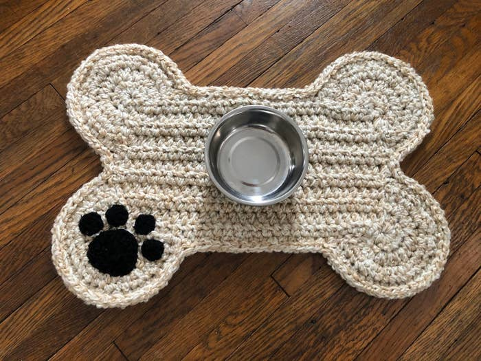 A bone-shaped crochet place mat with a paw print stitched on the bottom left, and a bowl set in the middle