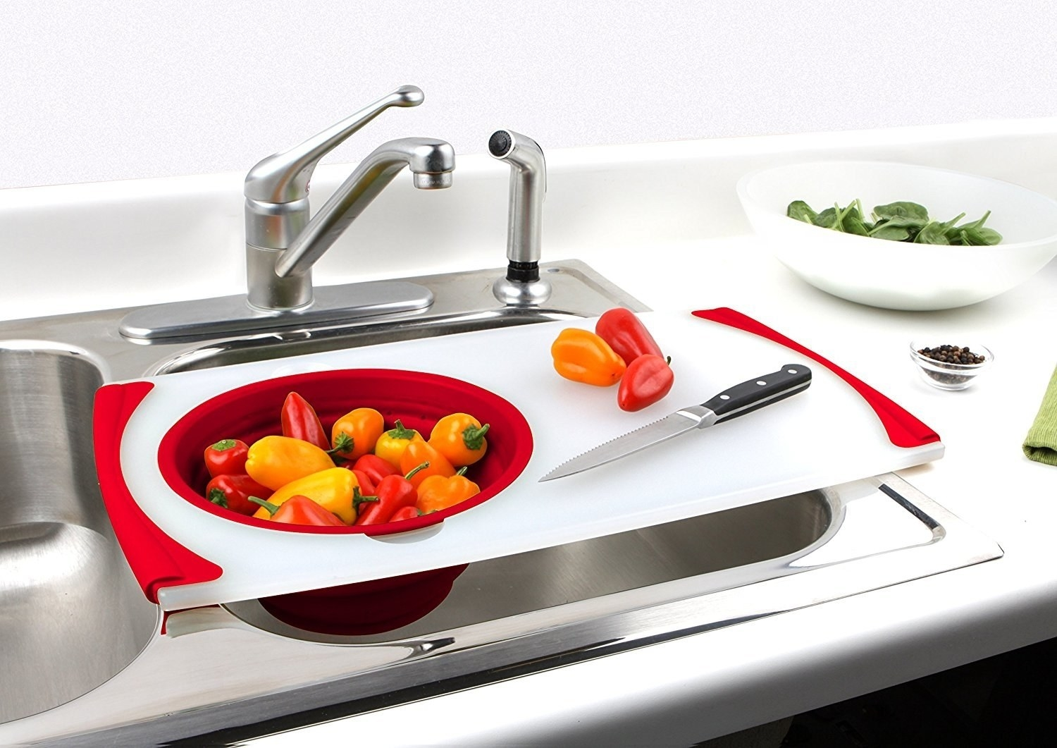 a white cutting board with red accents and a strainer set on one side of it to place over the sink for drainage