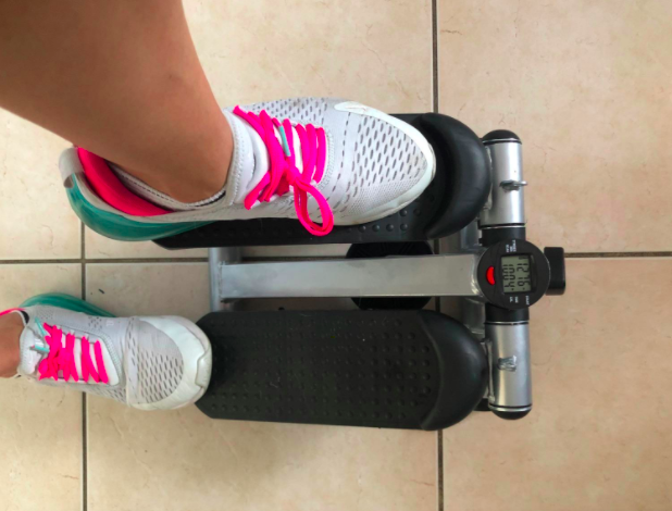 Reviewer steps on mini black stepping machine with white, gray, and pink sneakers