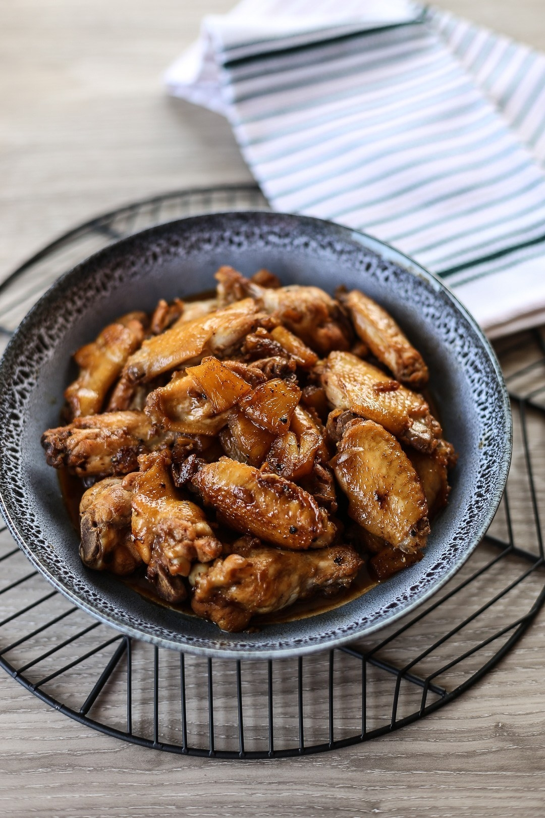 A textured blue bowl full of browned and glazed, sticky looking chicken wings
