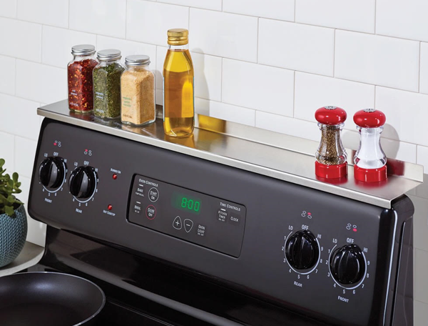 Product photo showing the stainless steel Stove Shelf above a stove with spices, salt and pepper, and olive oil resting on it