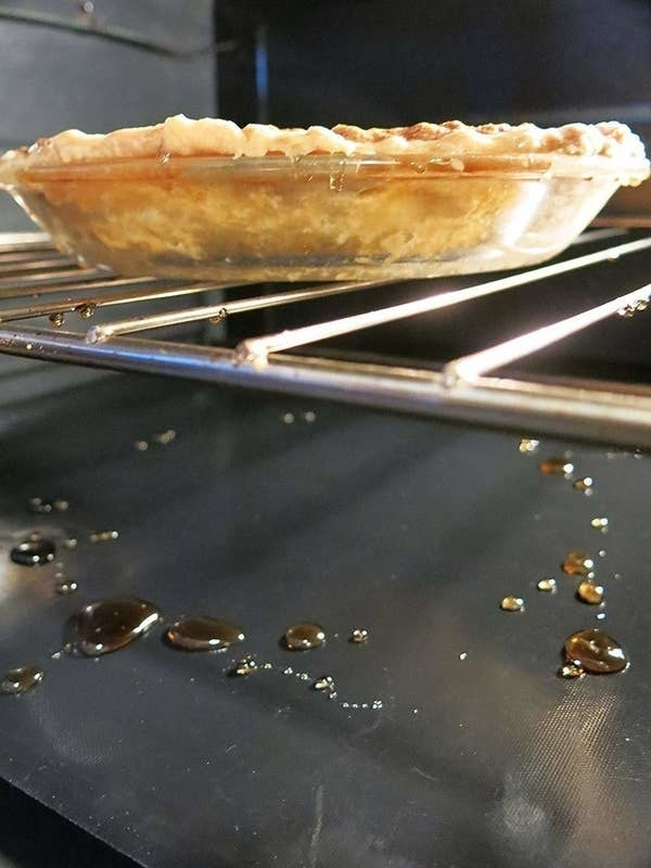 an apple pie inside the oven that has dripped liquid onto a mat below it