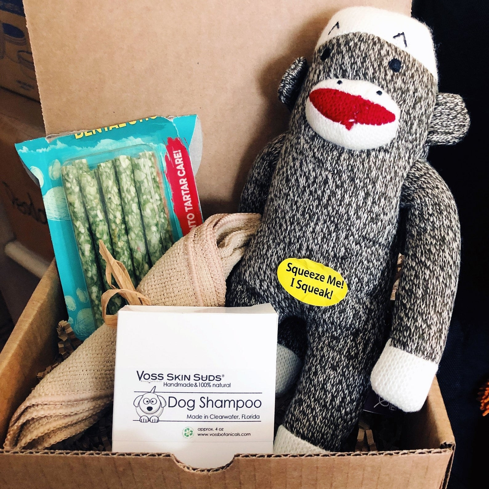 A box with a monkey toy, natural shampoo,  a wash cloth, and dental sticks