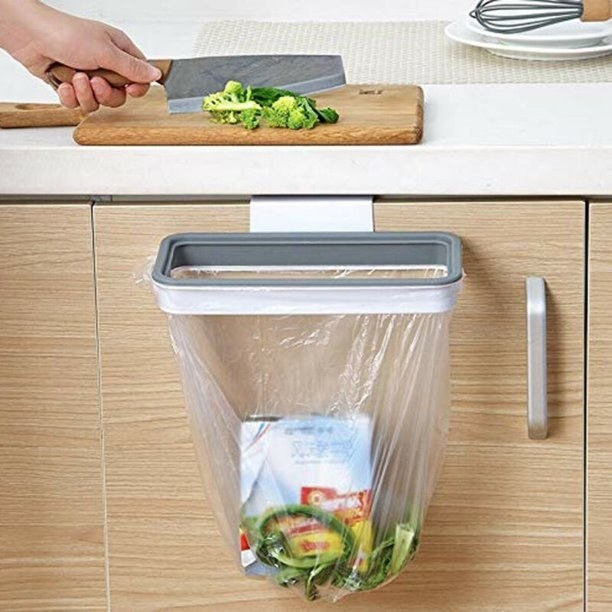 Product photo showing a person sliding vegetable scraps into the plastic bag holder attached to a cupboard door just below the countertop