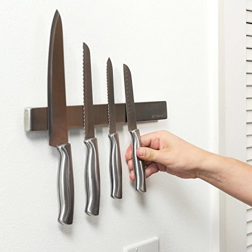 Product photo showing 15-inch magnetic knife holder with four knives attached to it
