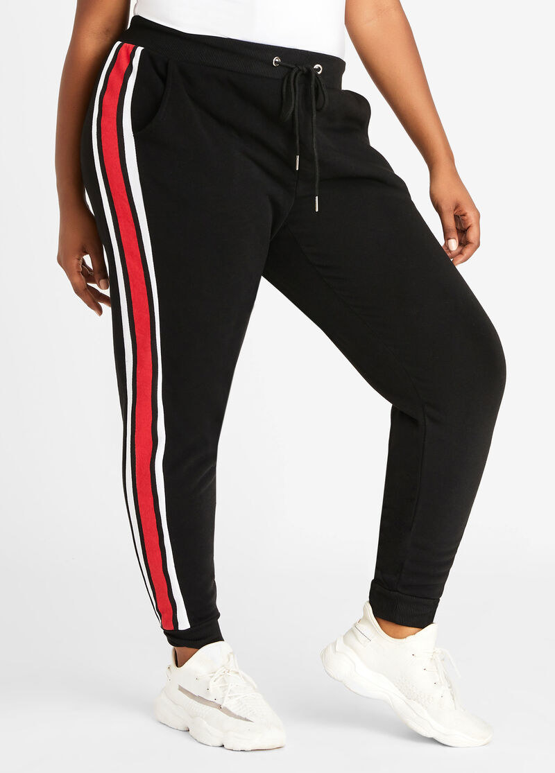 model in black joggers with red and white striped down the sides