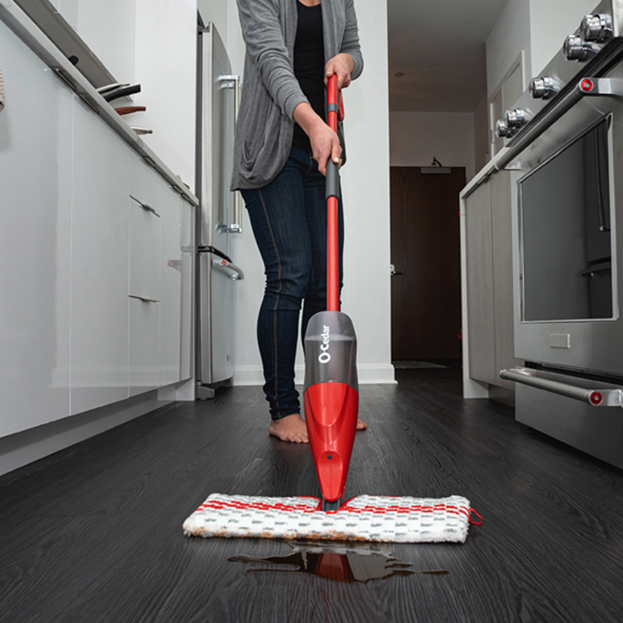 Product photo showing model using the O-Cedar ProMist Microfiber Spray Mop to clean up a spilled liquid
