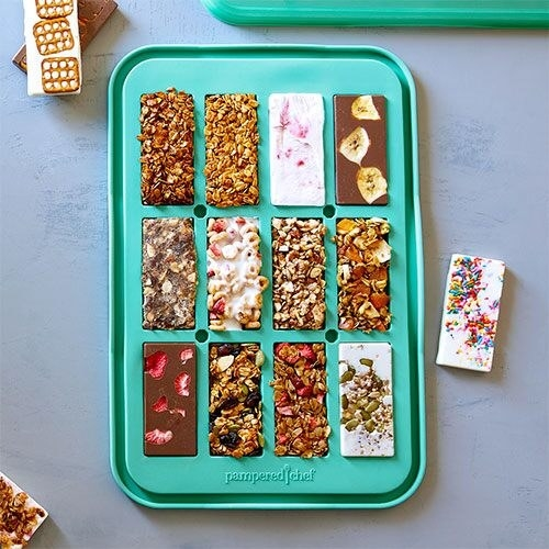 a teal green snack bar mold filled with various homemade treats