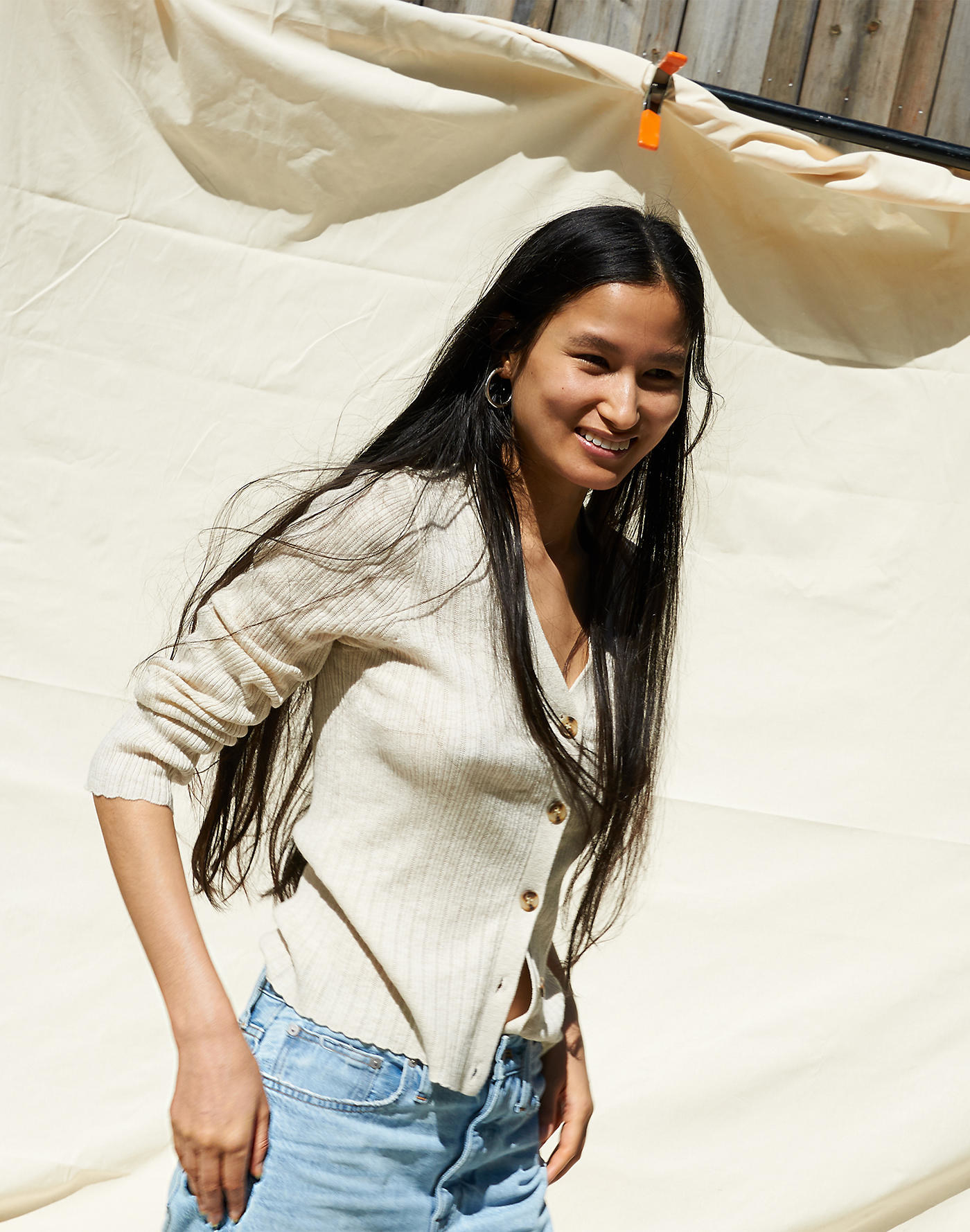 Model wearing the white ribbed v-neck cardigan with the buttons closed and a pair of jeans
