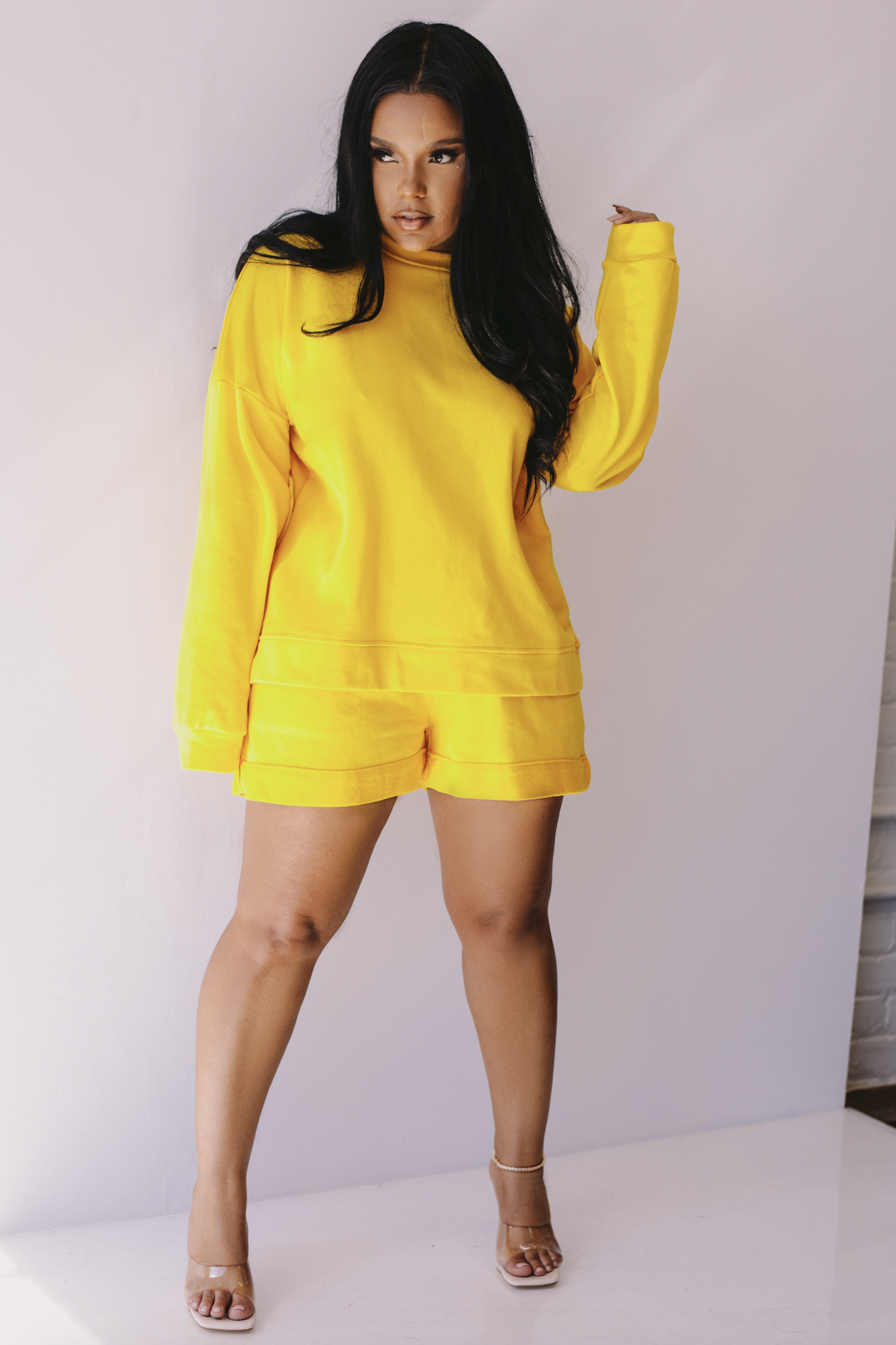 model in yellow crewneck sweatshirt and matching shorts