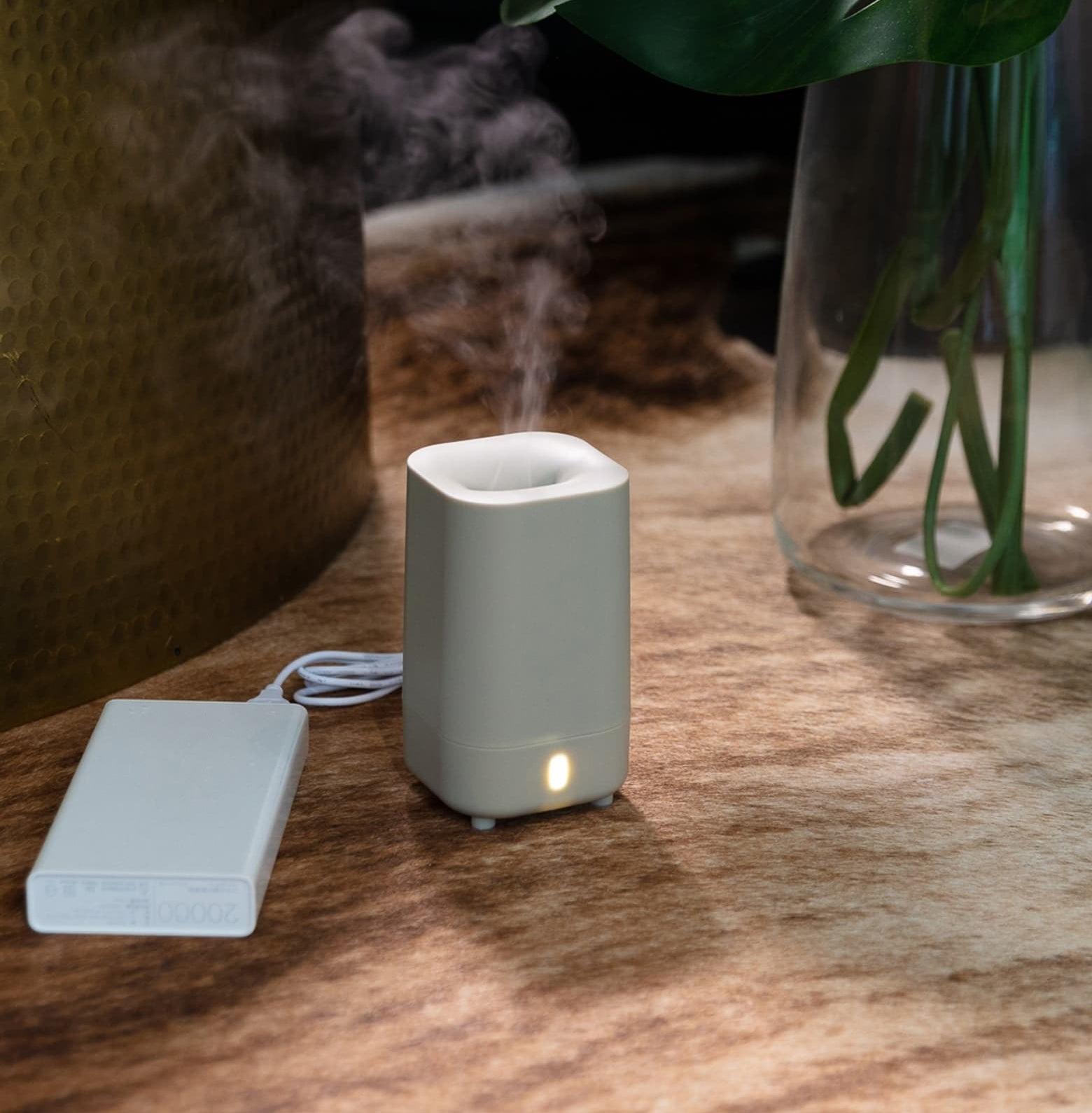 The small diffuser sitting on a table with mist coming out of the top and a battery pack sitting next to it