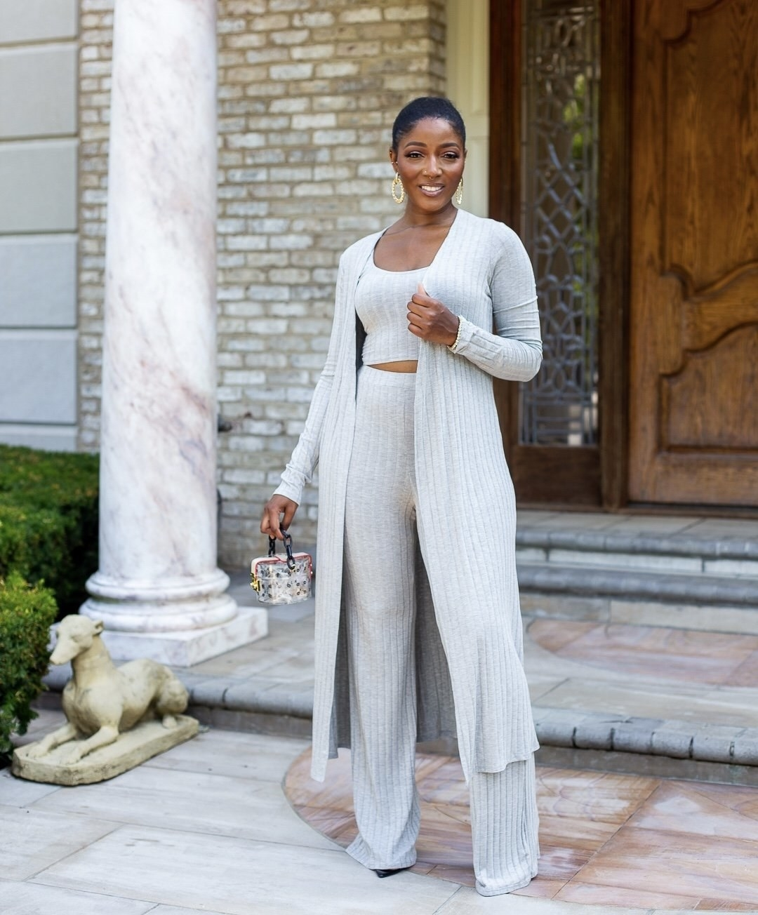 Model wearing wide-leg ripped pants, cropped tank and calf-length open cardigan in grey