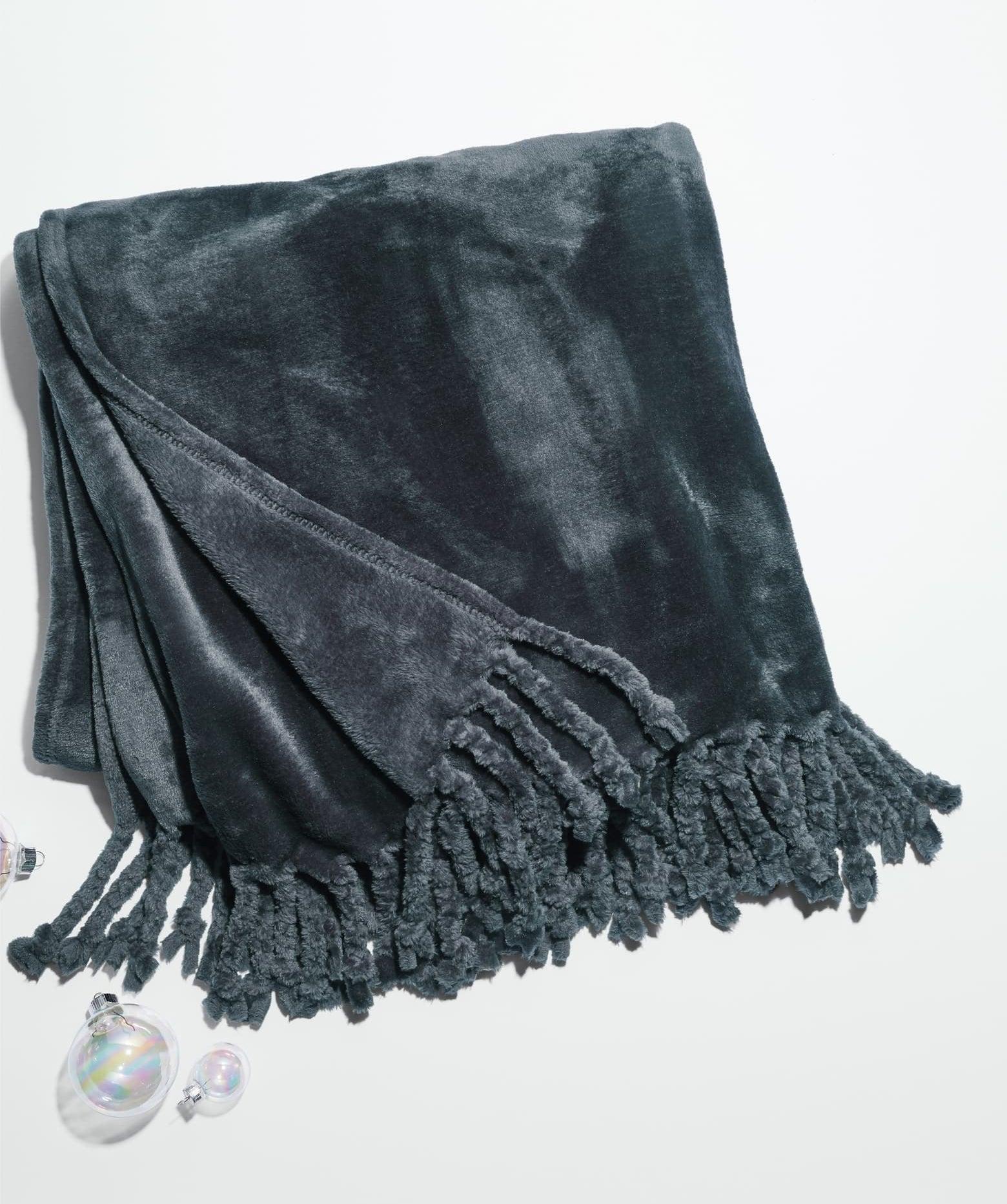 Grey plush blanket with fringe on the end
