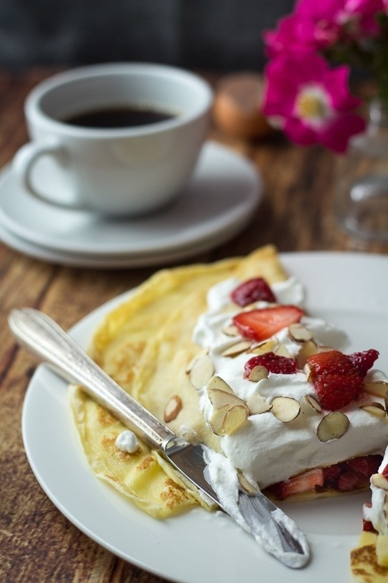A thin pancake topped with fluffy whipped cream, strawberries, and slivered almonds