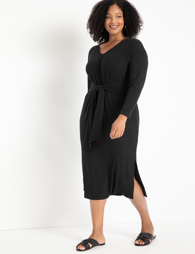 Model wearing the dress in black  with tie around the middle and small slits up the side