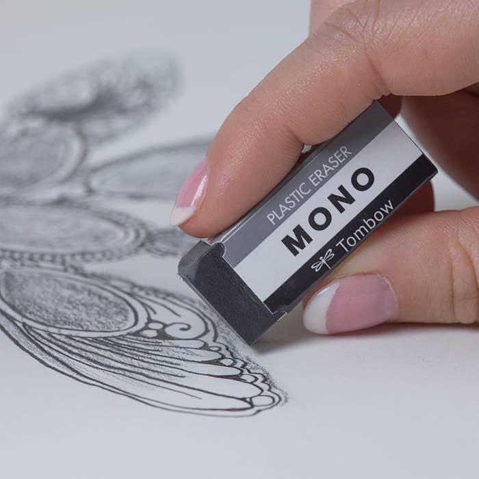 A hand holds an eraser beside a drawing