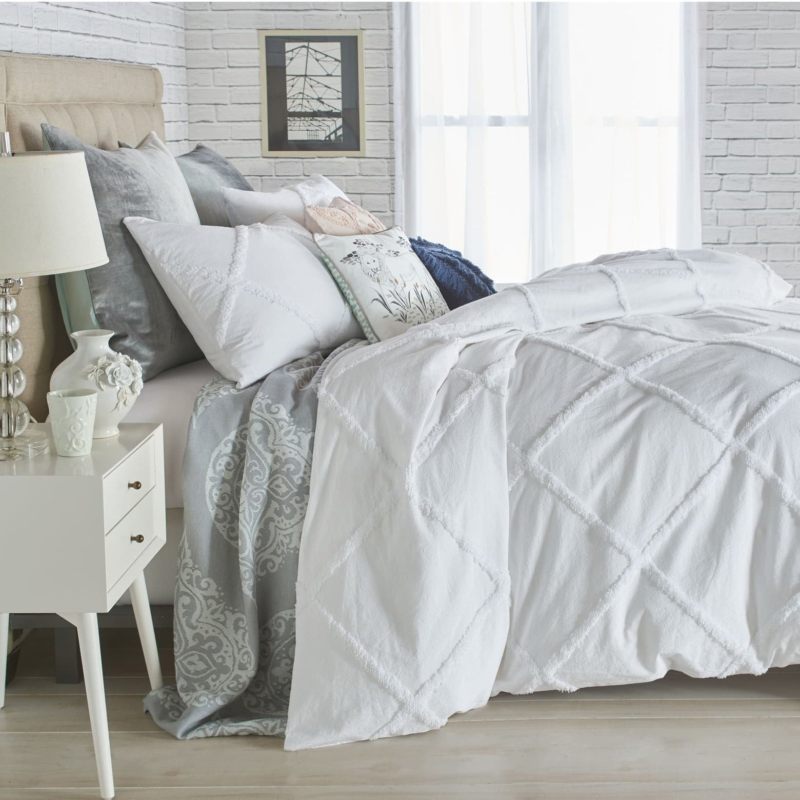 The white lattice duvet cover over a duvet on a bed with assorted pillows on it