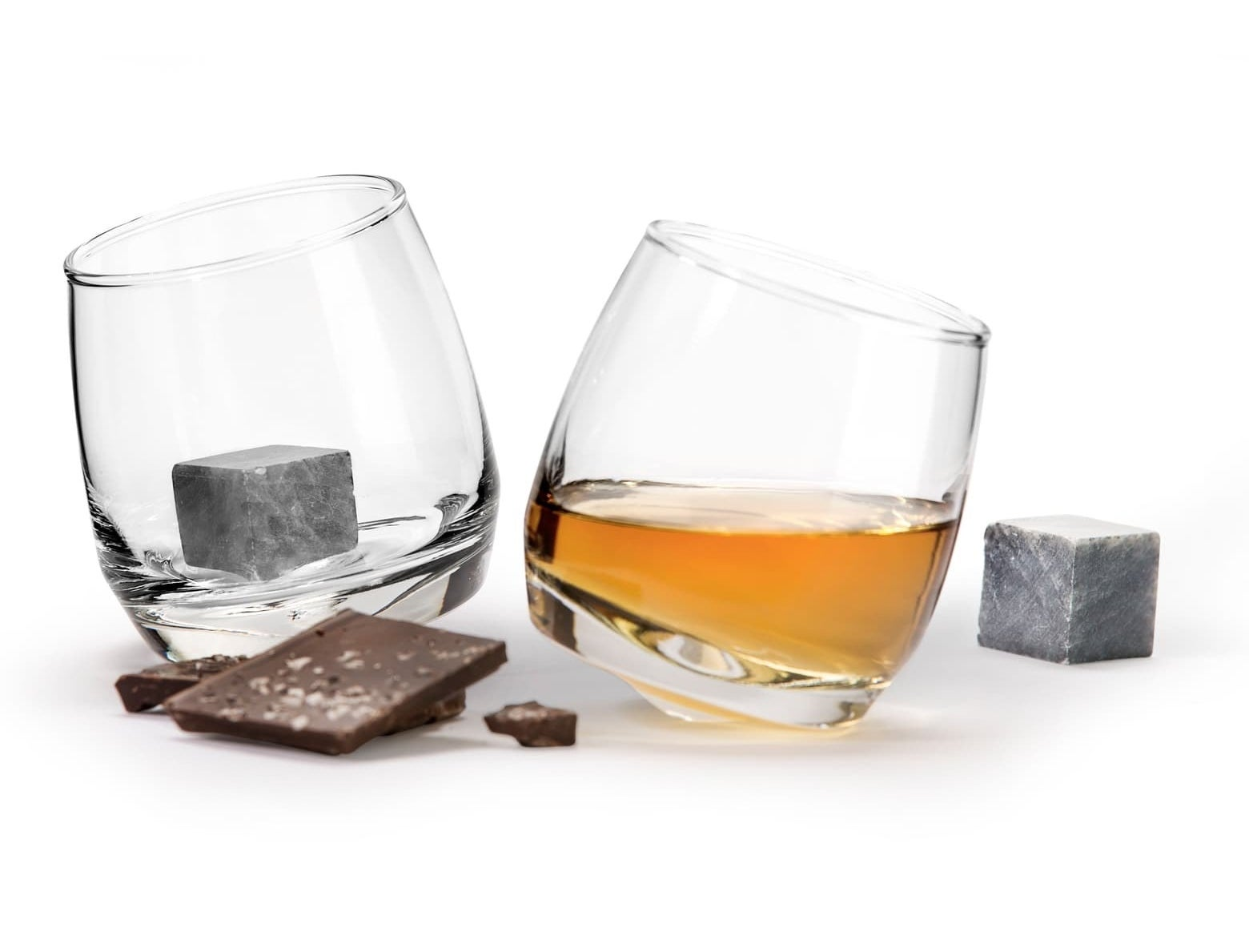 The two glasses one with liquid in it and one with the stone inside and the other stone sitting next to the glasses