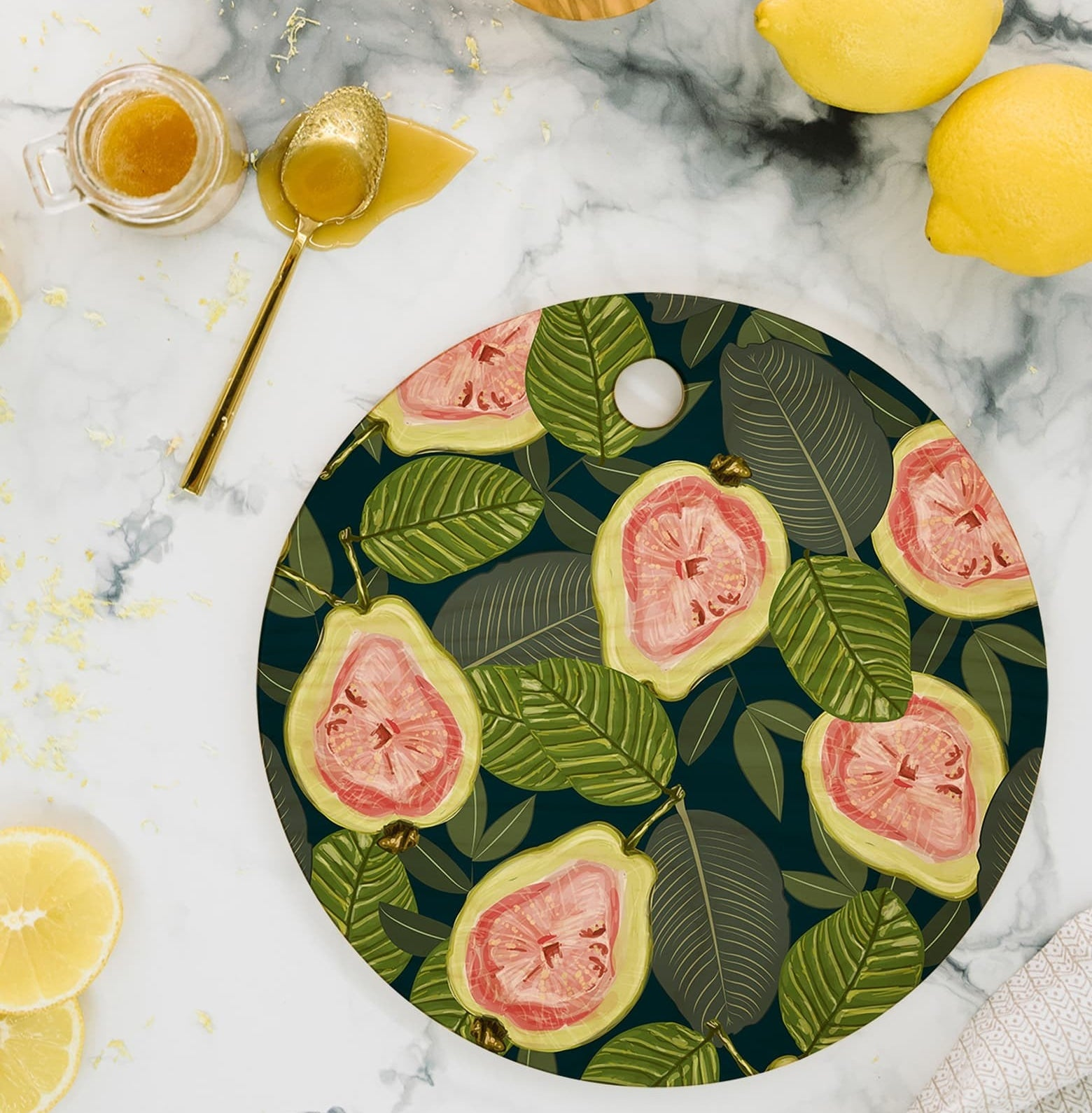 Round cutting board with illustrations of the insides of guavas and green leaves all over