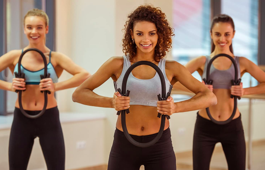 Three models each squeeze a black Pilates ring while attending a class