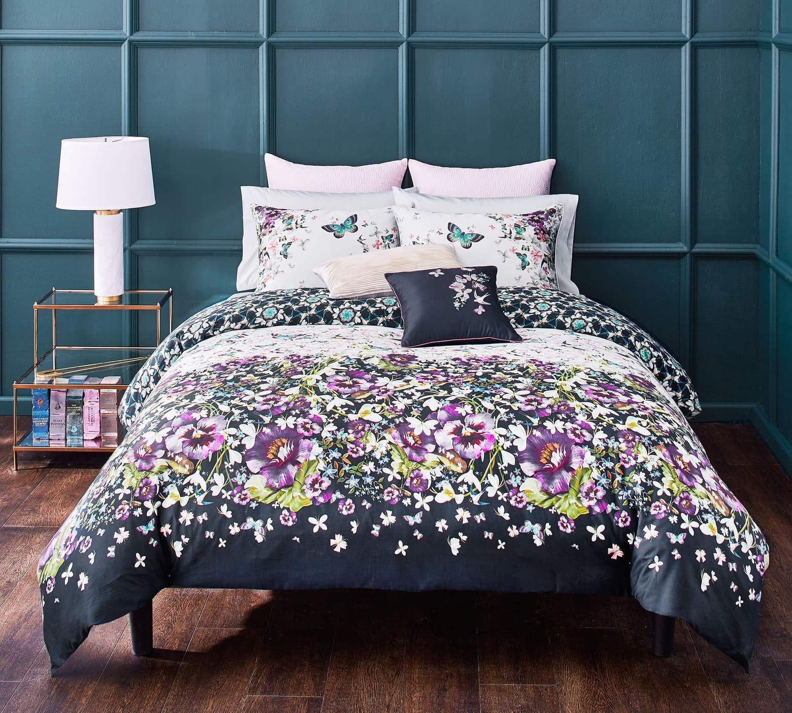 Floral comforter in navy with purple and green flowers all over it on a bed with pillows with floral and butterflies on them