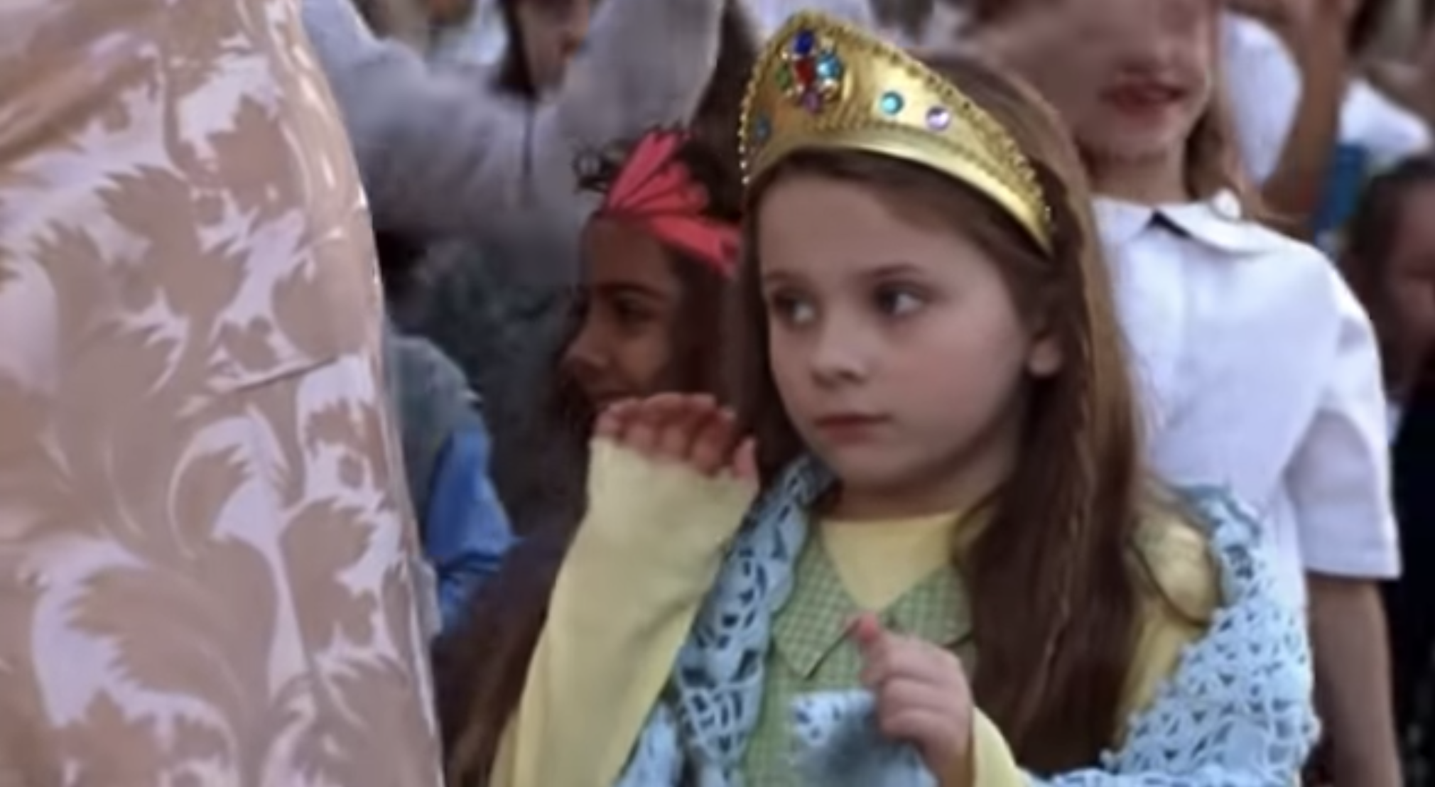 Carolina walking and waving alongside Princess Mia in the Genovian Independence Day parade.