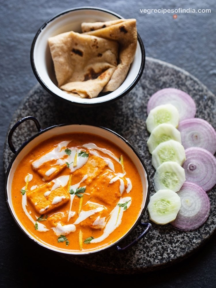 A pot of buttery, spiced curry dotted with soft paneer cheese next to a bowl of fluffy, charred naan and fresh veggies