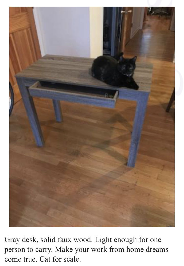 """An advert for a simple desk with a cat on it. Advert reads, """"Gray desk, solid faux wood. Light enough for one person to carry. Make your work from home dreams come true. Cat for scale."""""""