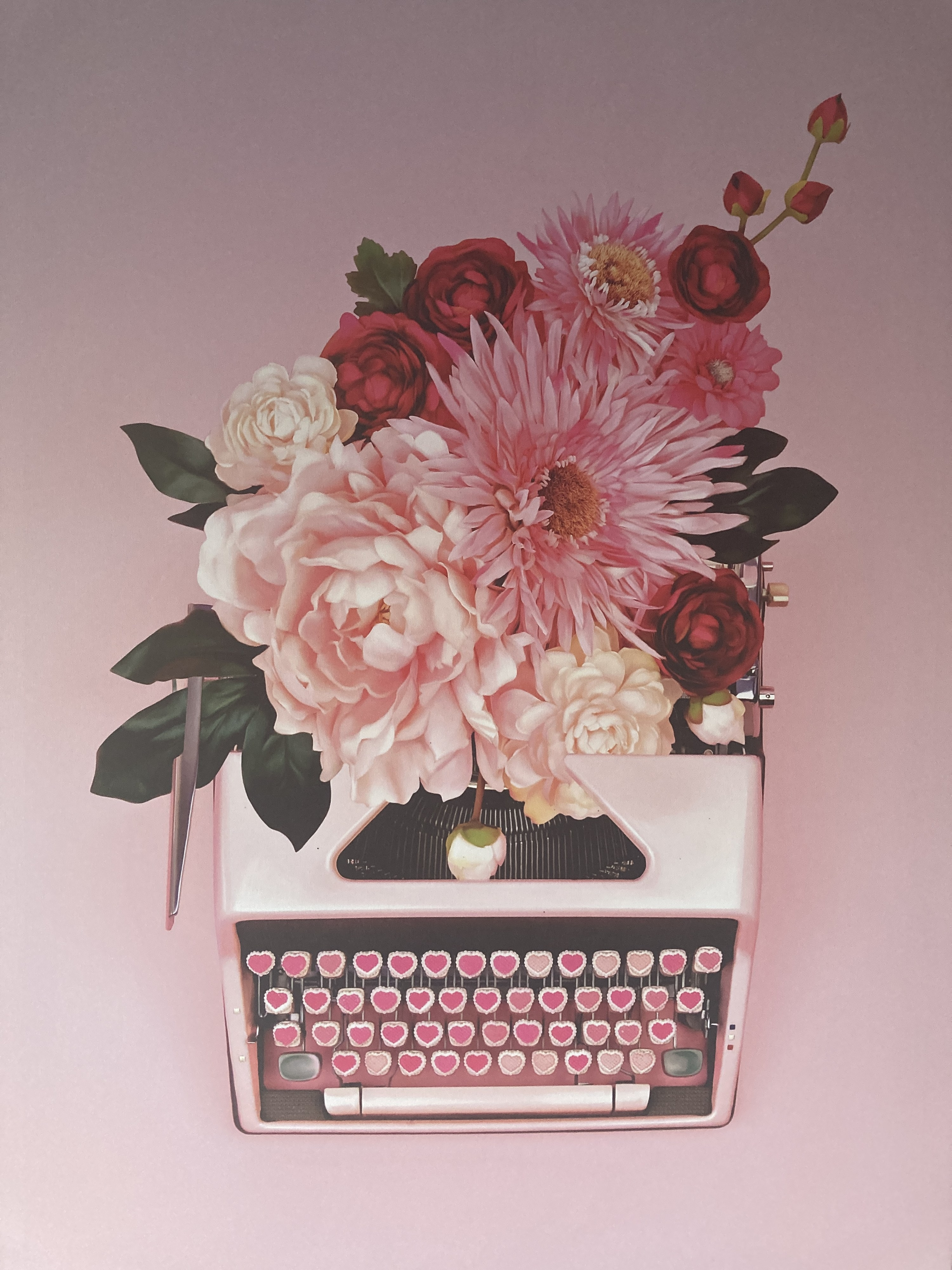 A canvas with a typewriter with flowers coming out the top