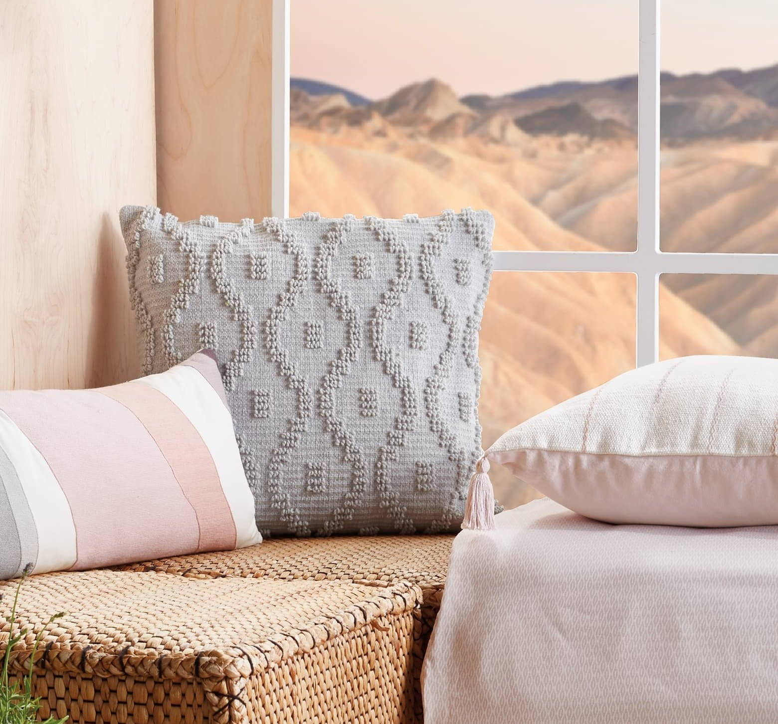 The grey throw pillow with embroidered pattern on the front sitting on a bench