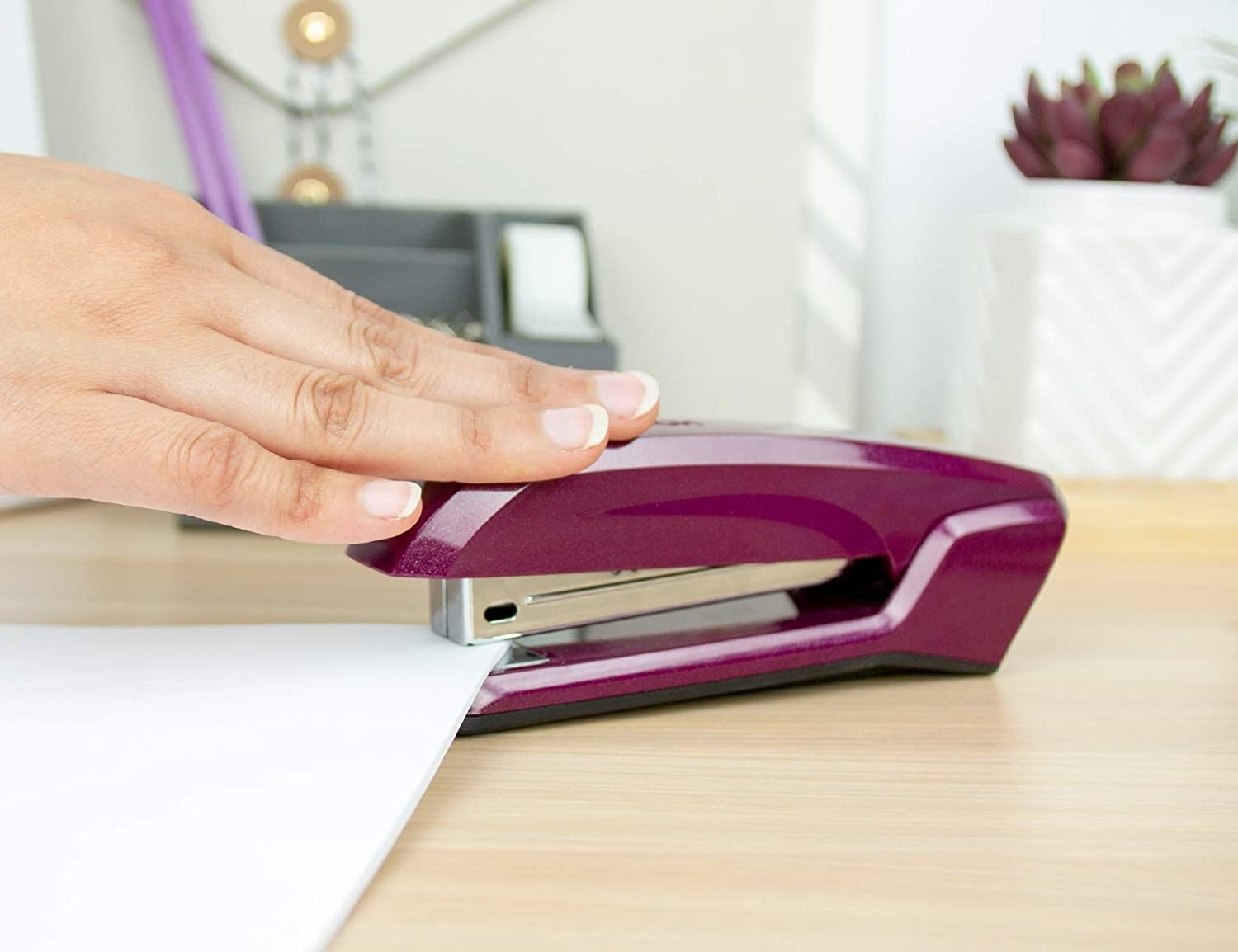 A hand pushes a stapler over a paper