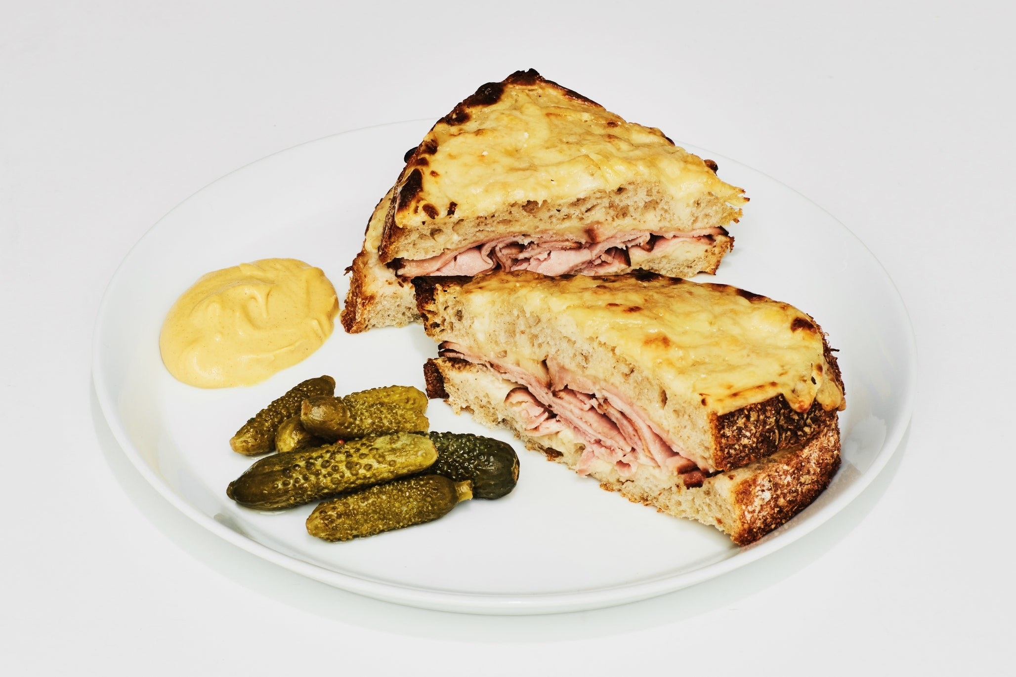 A sandwich made of thick slices of bread, melty cheese, and thin ham on a plate with a side of small pickles and dijon mustard