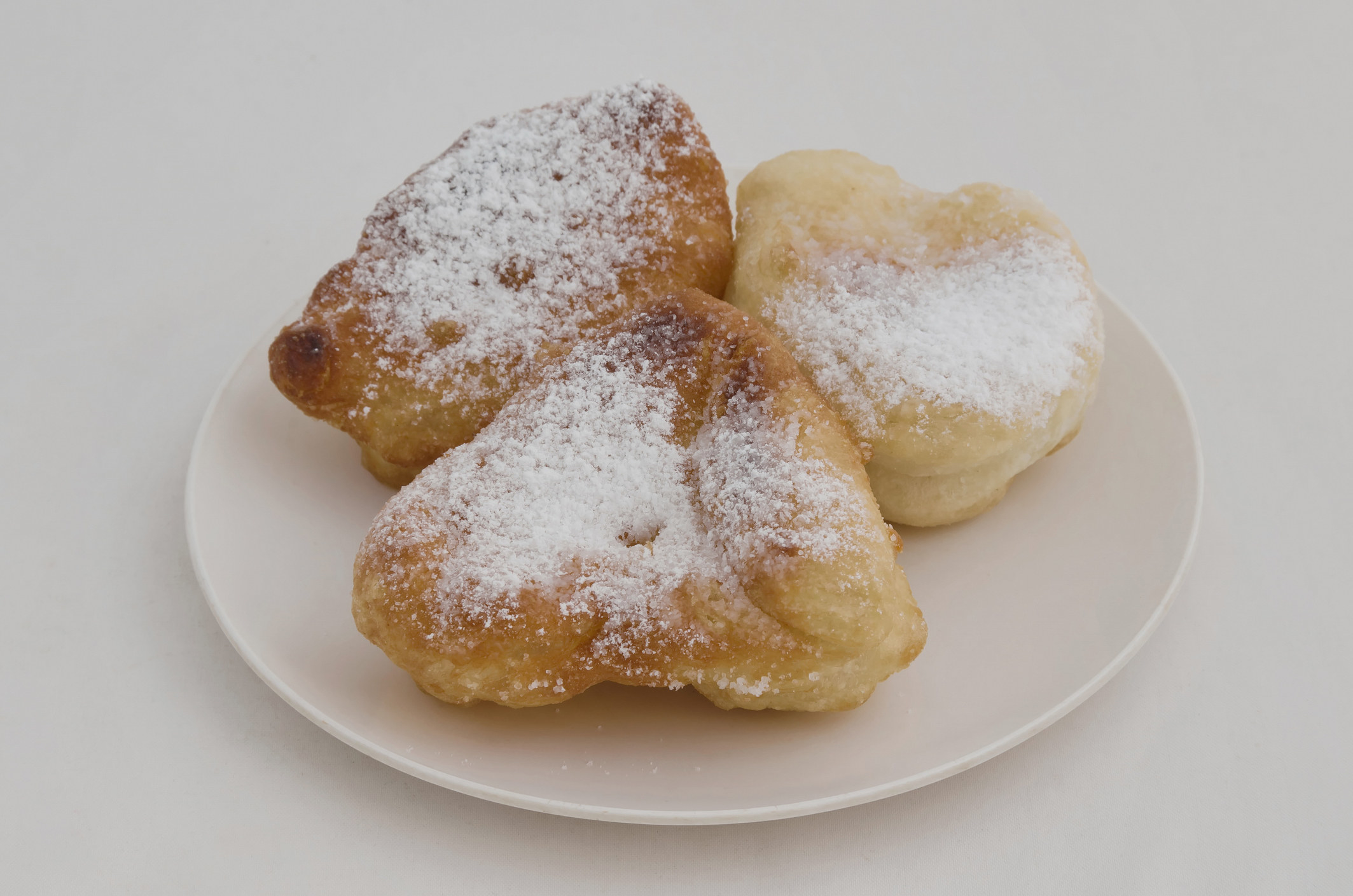 plate of three fried balls of dough sprinkled with powdered sugar