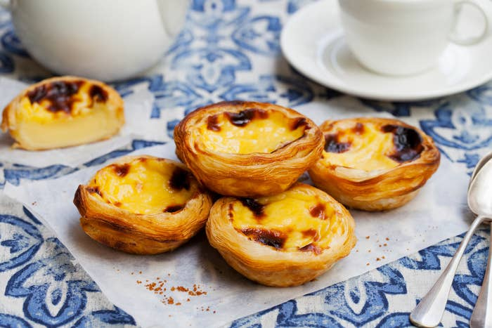 palm-sized egg custard tarts with flaky pastry on a patterned table