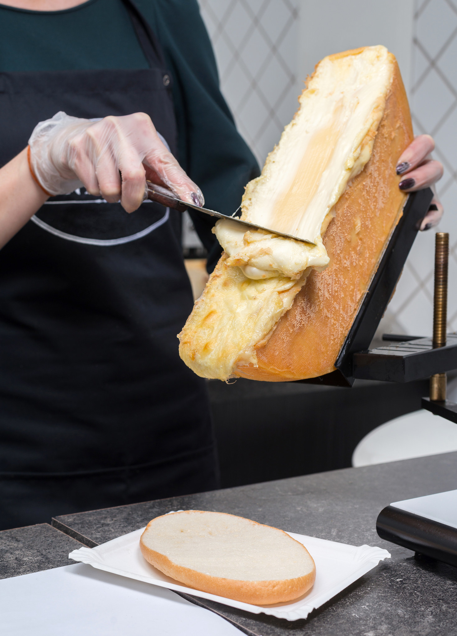 half a wheel of gooey melted cheese being scraped onto a piece of bread