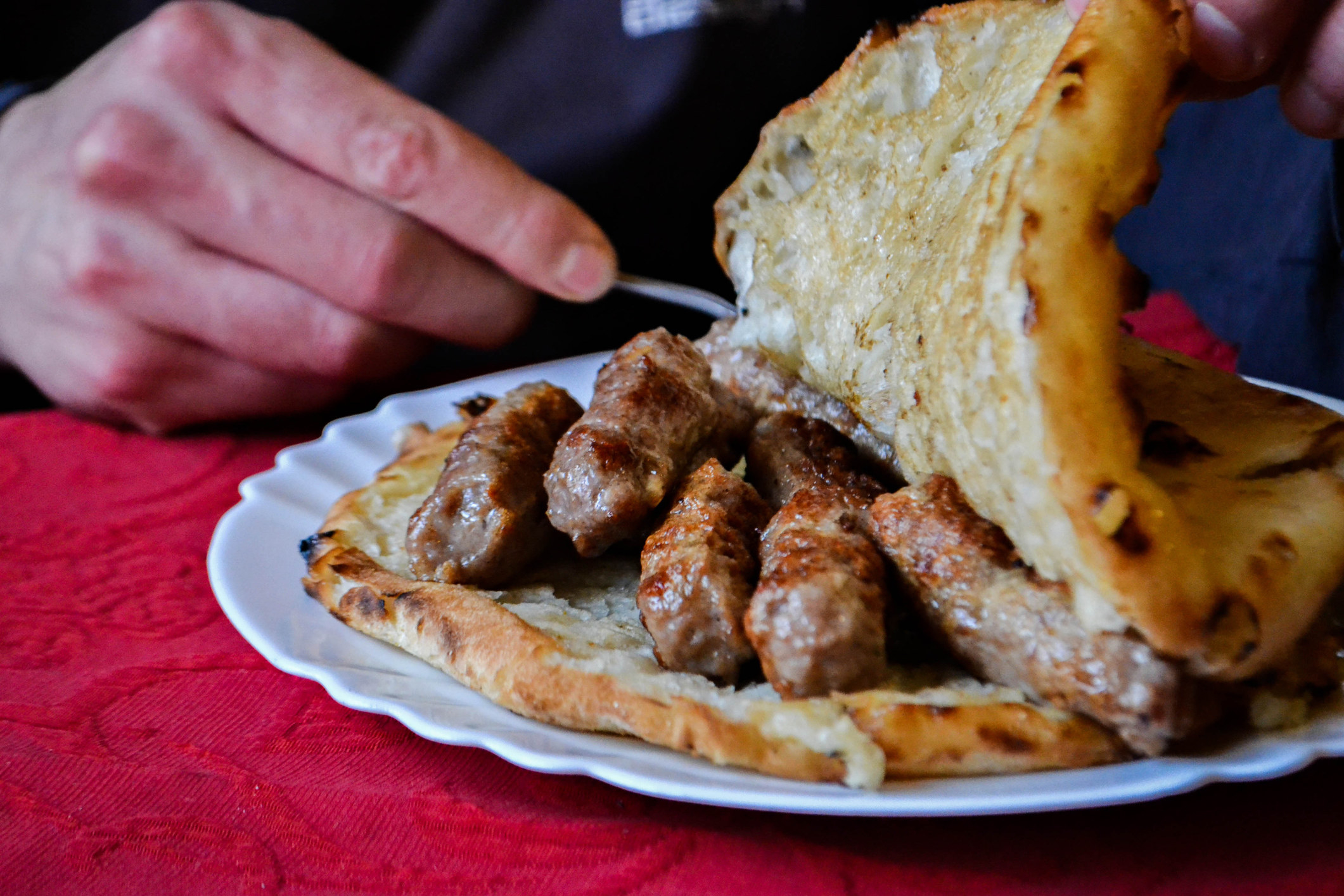 logs of grilled meat inside a thick pita-like bread