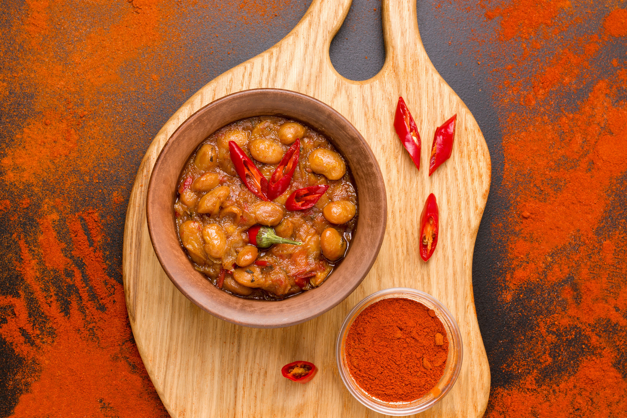 hearty bean stew in a bowl on a wooden board with chilli garnish