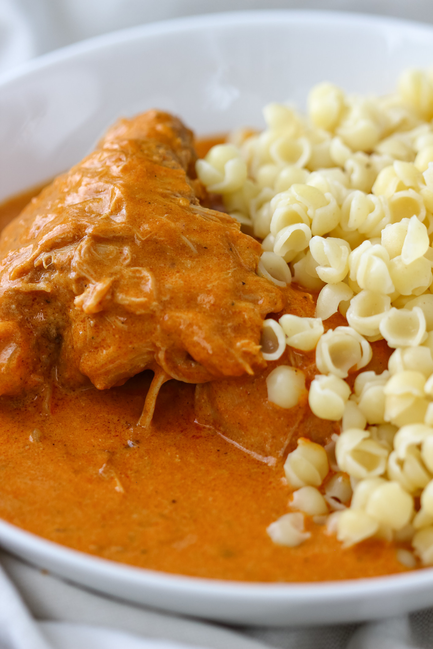 tender piece of chicken on the bone with a creamy orange paprika sauce and small shell-shaped pasta on the size