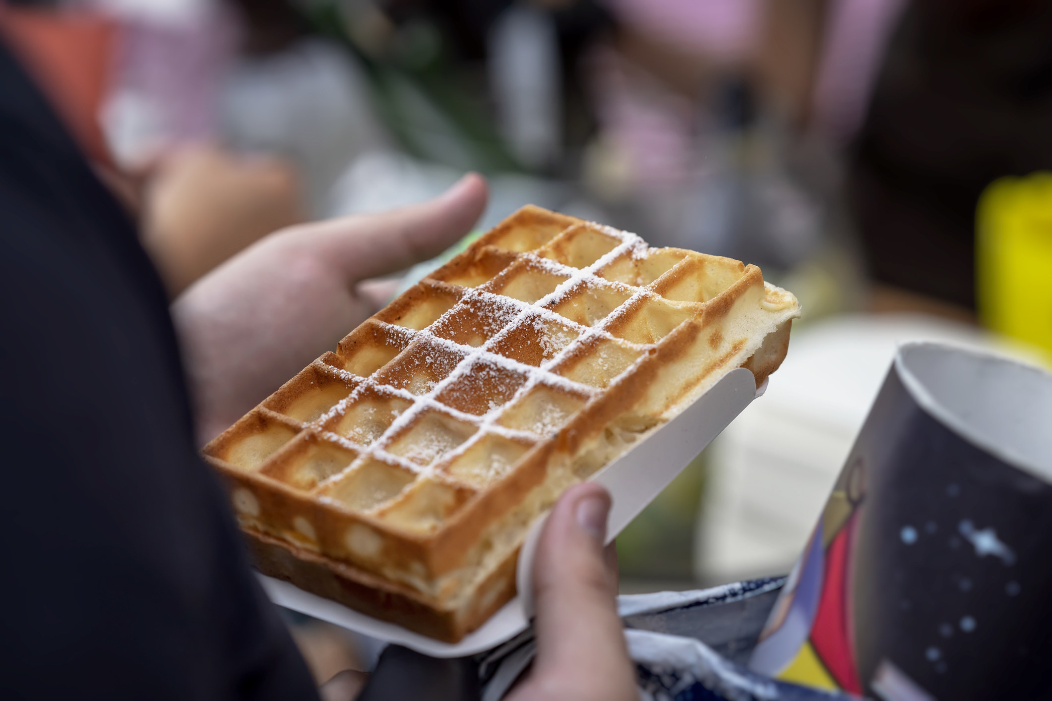 golden brown waffle topped with light sprinkling of powdered sugar