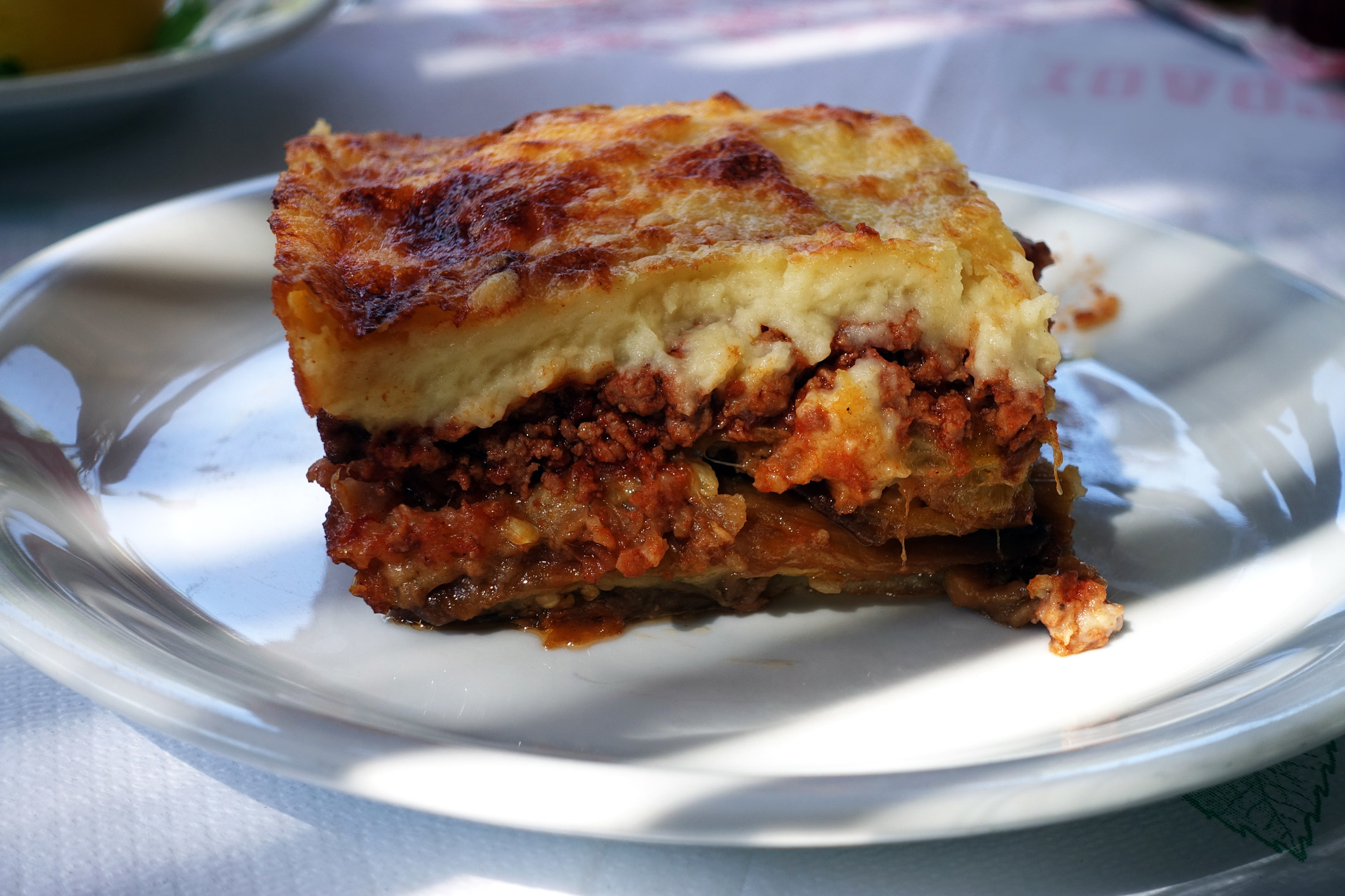 big slice of moussaka with a golden brown top, served on a white plate