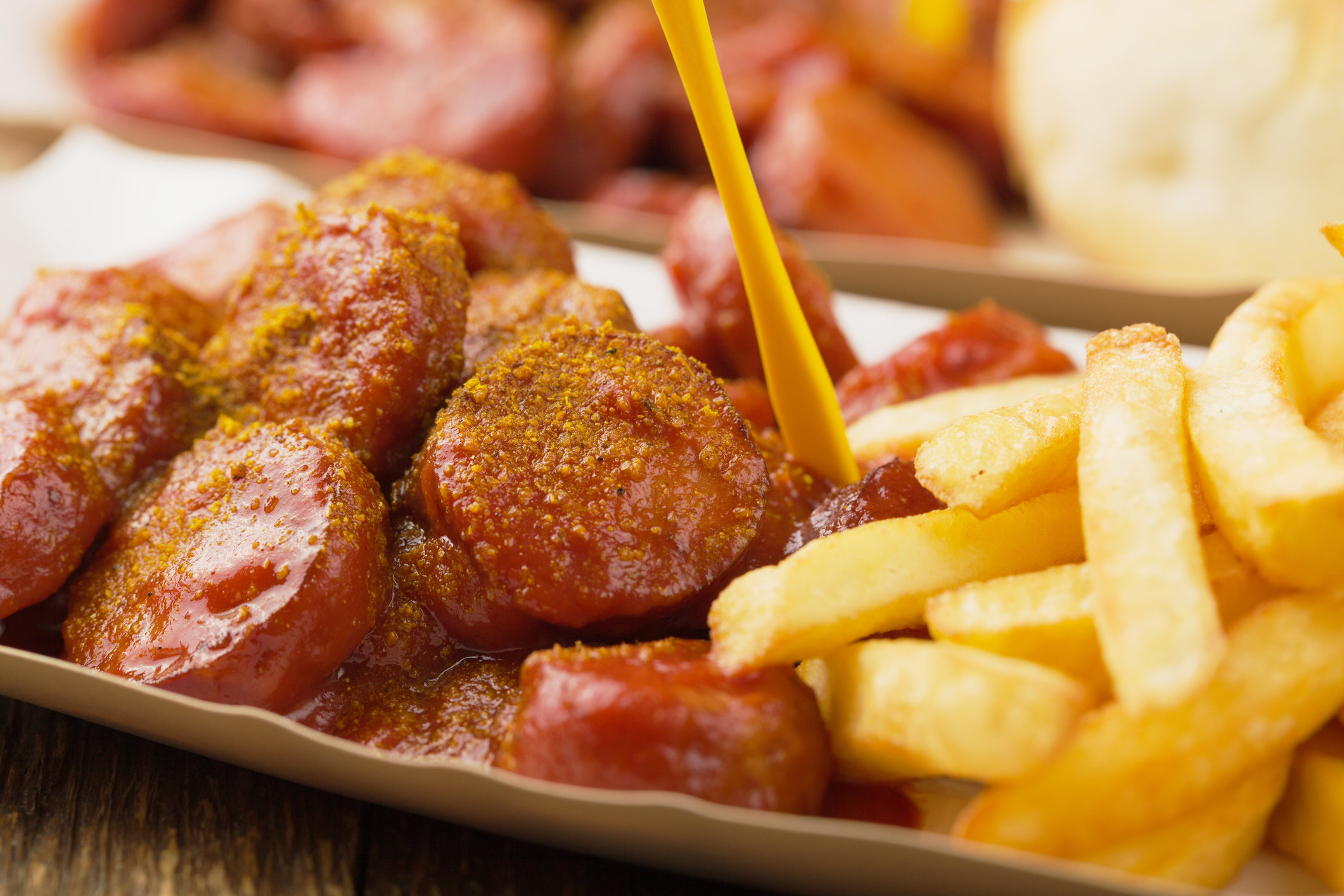 chopped up sausages sprinkled with curry powder and a pile of french fries