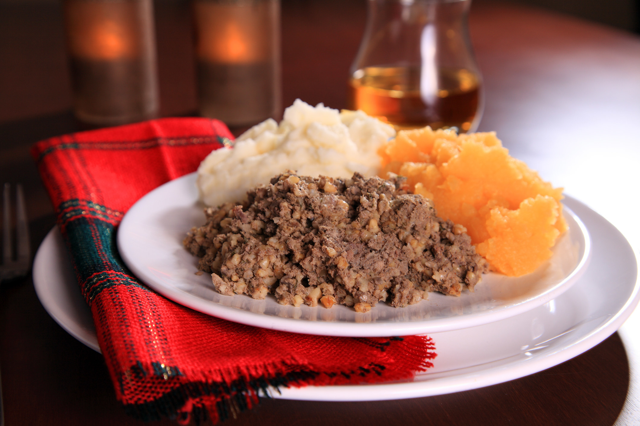 a plate of haggis with mashed potatoes and other mashed vegetables